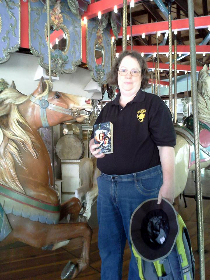Bridget Gehrling: So here I am, on the Forrest Park Carousel, newly restored in Queens, NY, with the Liaden book I am currently re-reading and wearing my new favorite shirt.